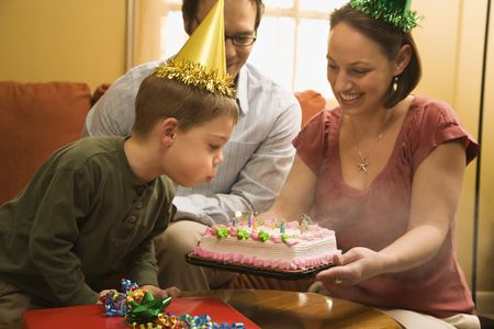 party hat: Caucasian boy in party hat blowing out candles on birthday cake with family watching. Stock Photo