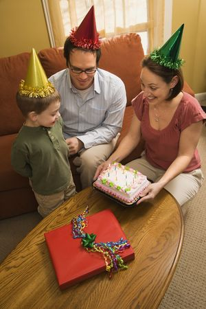 Caucasian boy in party hat with Birthday cake and family. photo