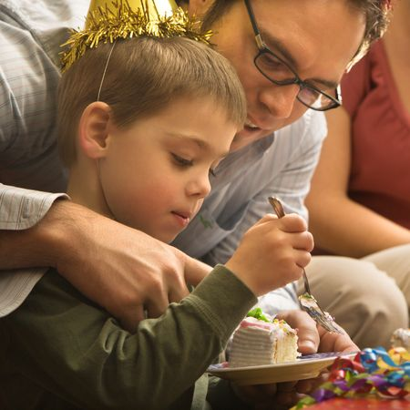 Caucasian mid adult father helping son with birthday cake. Stock Photo - 2190113