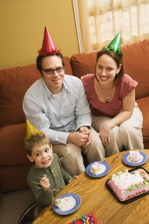 Caucasian boy and parents in party hats eating birthday cake. Stock Photo - 2190146