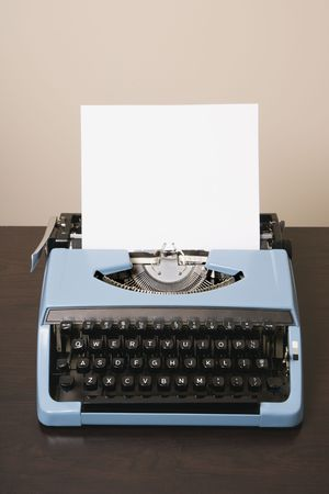 writers block: Still life of blank sheet of paper in an old fashioned typewriter.