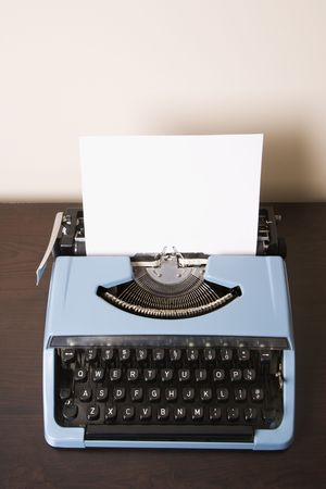 Still life of blank sheet of paper in an old fashioned typewriter. photo
