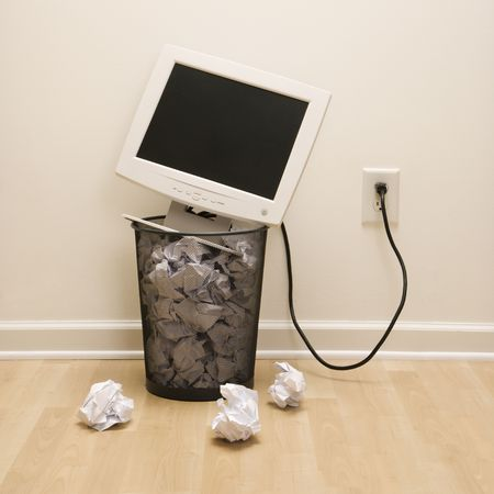 the computer monitor: Computer monitor in trash can surrounded by crumpled up paper.