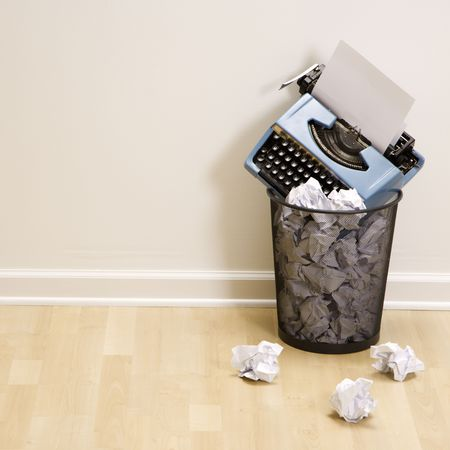 writers block: Old fashioned typewriter in trash can surrounded by crumpled up paper. Stock Photo