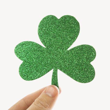 saint paddy's: Hand holding a green glitter paper shamrock.