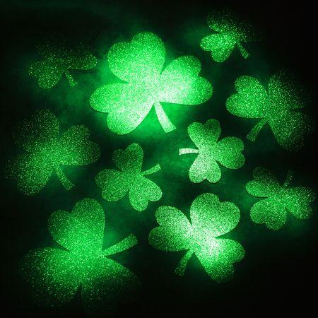 saint paddy's: Group of green shamrocks reflecting light on black background.