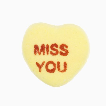 miss: Yellow candy heart that reads miss you against white background.