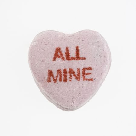 message: Purple candy heart that reads all mine against white background.
