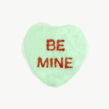 Green candy heart that reads be mine against white background.
