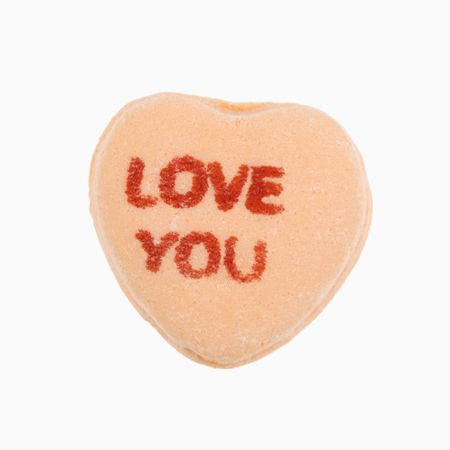 love image: Orange candy heart that reads love you against white background. Stock Photo