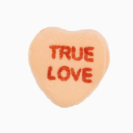 that: Orange candy heart that reads true love against white background.