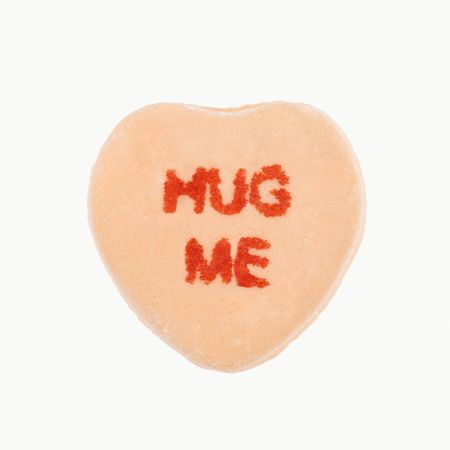 love image: Orange candy heart that reads hug me against white background.