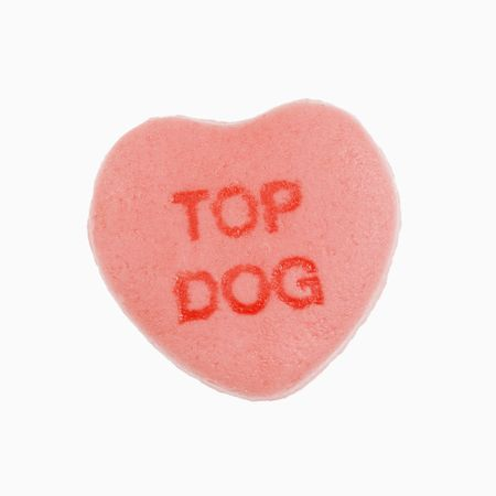 that: Pink candy heart that reads top dog against white background.