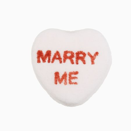 marry me: White candy heart that reads marry me against white background.
