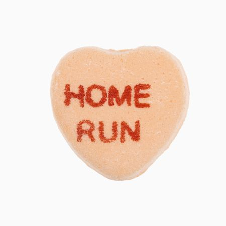 home run: Orange candy heart that reads home run against white background. Stock Photo