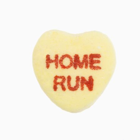 home run: Yellow candy heart that reads home run against white background.