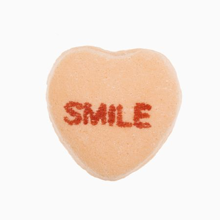 that: Orange candy heart that reads smile against white background.