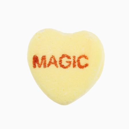 Yellow candy heart that reads magic against white background. photo
