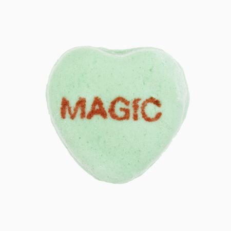 Green candy heart that reads magic against white background. photo