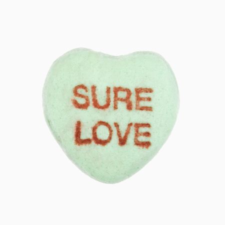 that: Green candy heart that reads sure love against white background.