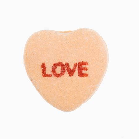 Orange candy heart that reads love against white background. Stock Photo - 2191245