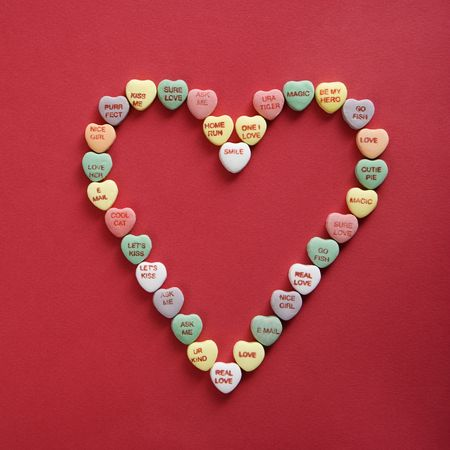 Colorful candy hearts with sayings on them arranged in shape of heart on red background. Stock Photo - 2190096