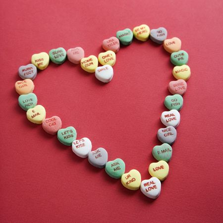 Colorful candy hearts with sayings on them arranged in shape of heart on red background. Stock Photo - 2190157