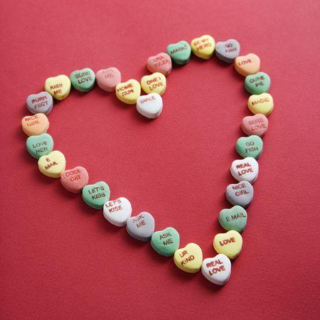Colorido dulces corazones con refranes de ellos dispuestos en forma de corazón sobre fondo rojo.  Foto de archivo - 2190157