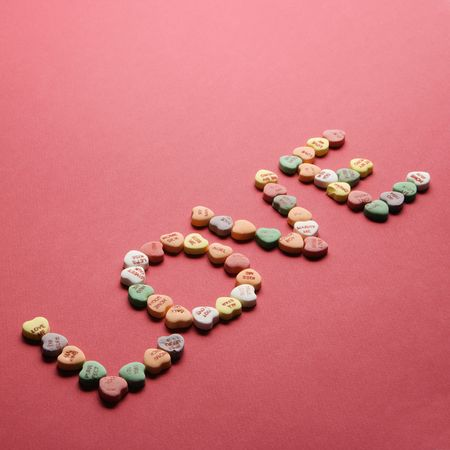 them: Colorful candy hearts with sayings on them arranged to spell the word love.