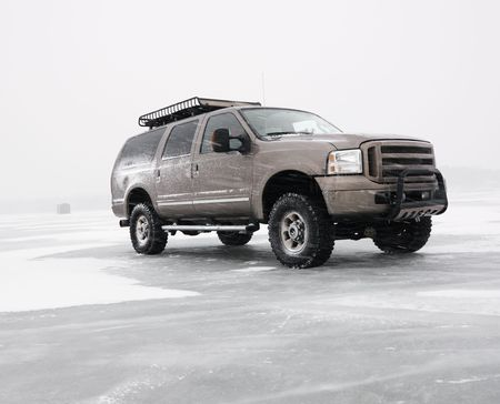 rack wheel: Four wheel drive truck with all terrain tires and roof rack parked on desolate frozen lake in Green Lake, Minnesota, USA.