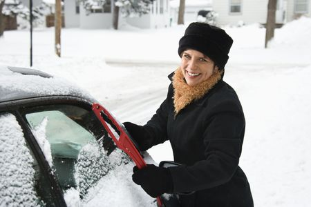 scraping: Caucasian mid adult woman scraping ice off car windshield and smiling at viewer.