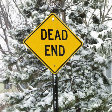 end road: Snowy scene in suburb with evergreen trees and dead end road sign. Stock Photo