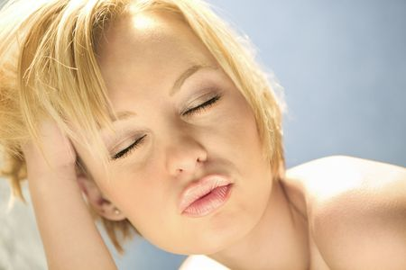 puckered: Head and shoulder portrait of  attractive young adult Caucasian blond woman with lips puckered. Stock Photo