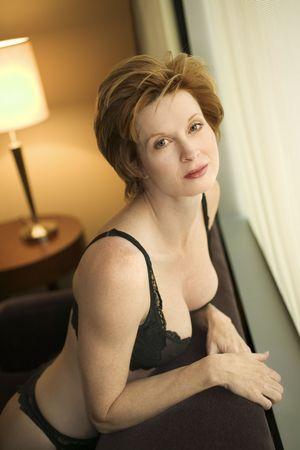 Pretty Caucasian woman in lingerie kneeling by window looking at viewer.