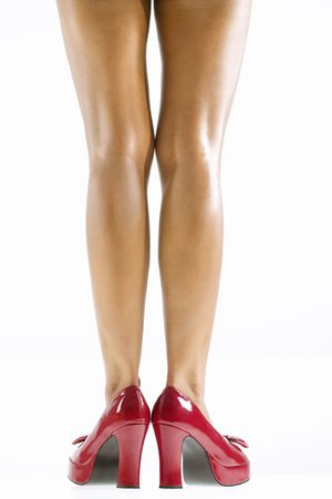 high heel shoes: Studio portrait of young Caucasian womans bare legs and red high heel shoes.