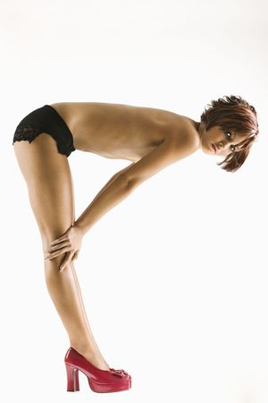 Studio portrait of young partially  Caucasian woman bending over. Stock Photo