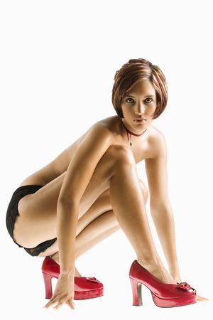 squat: Studio portrait of young partially  Caucasian woman kneeling.
