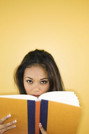 peering: Filipino young adult woman peering over book at viewer. Stock Photo