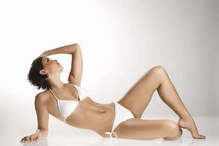 recline: Caucasian young adult woman in bikini reclining and looking up.