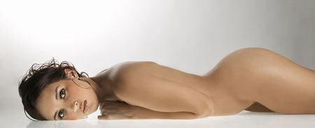 nude stomach: Nude Caucasian young adult woman lying on stomach  looking at viewer.