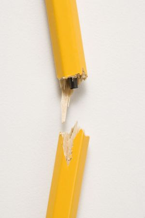 Wooden yellow pencil broken with lead exposed against white background. photo