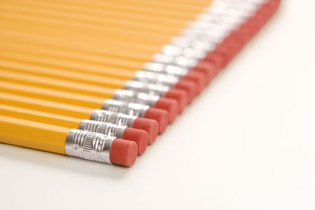 Eraser ends of group of pencils lined up in an even row.  photo