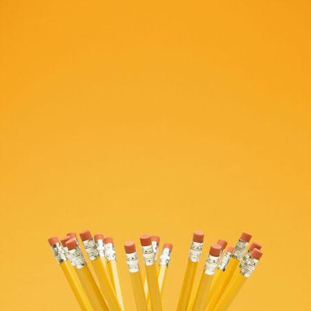 Group of eraser ends of pencils on orange background. photo