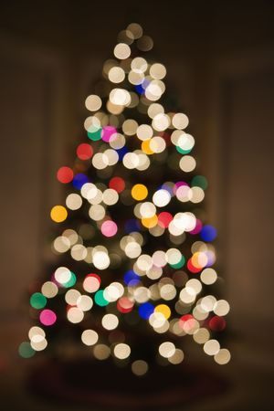 customs and celebrations: Abstract Christmas tree with blurred multicolored lights. Stock Photo