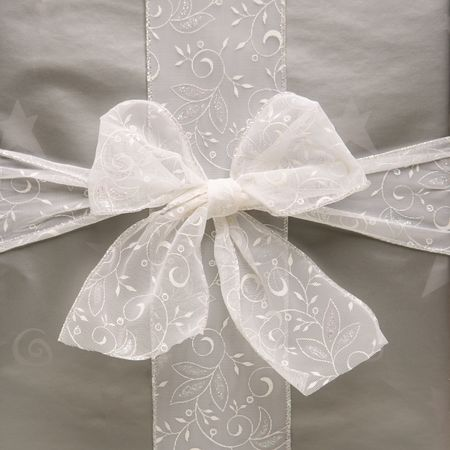 customs and celebrations: Close up of large silver wrapped Christmas gift with bow. Stock Photo