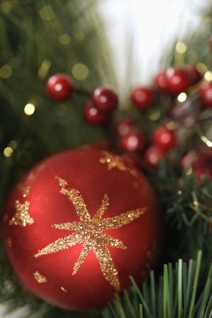 customs and celebrations: Close up of red ornament and berries on Christmas wreath. Stock Photo
