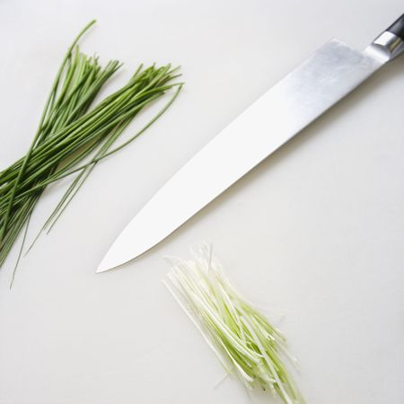 Fresh chives with kitchen knife resting on countertop. photo
