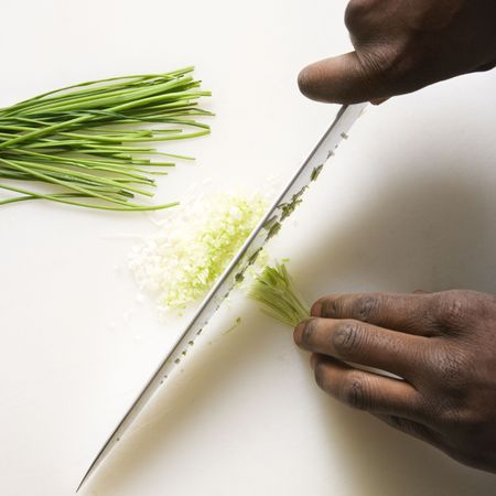 chives: African-American male hands using large kitchen knife to chop fresh chives. Stock Photo