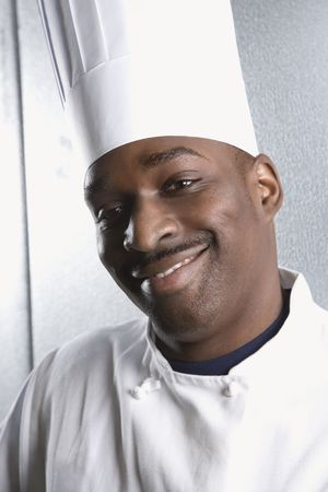 toque: Head shot of African-American male chef wearing traditional uniform and toque looking at viewer smiling. Stock Photo