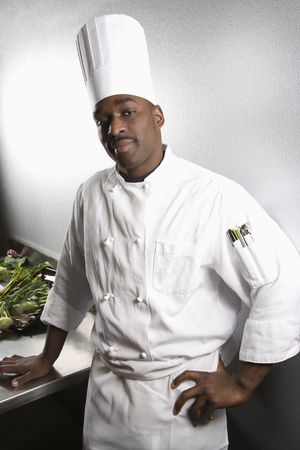 occupation: African-American male chef wearing traditional uniform and toque looking at viewer.